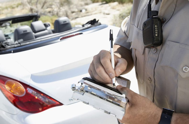 Officer writing a driver a ticket